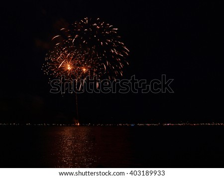 Long Exposure of Fireworks Reflecting on Calm Rippling Water - stock photo