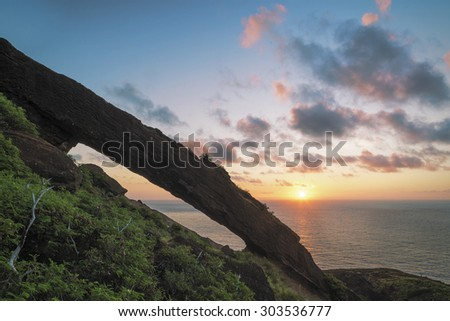 Long exposure of sunrise from the top of a popular hike on the east side of Oahu, Hawaii. The daytime long exposure creates a smooth surface over the ocean and a motion blur in the clouds.  - stock photo