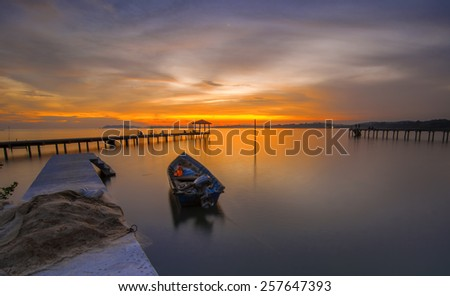 Long Exposure of Sunset Seascape. The boat a bit unsharp effect of long exposure shot - stock photo