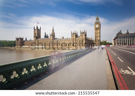 Long exposure of the Houses of Parliament in London with blue sky seen from the Westminster Bridge with some blurred people. - stock photo