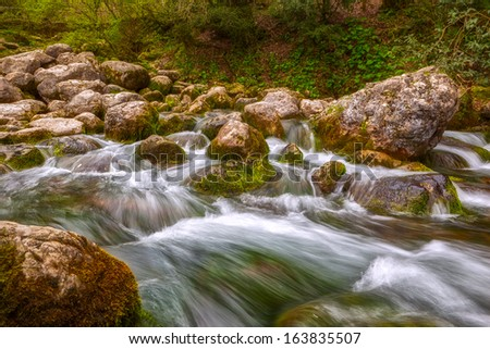 Long exposure photo of mountain river water stream over rocks in the forest.  - stock photo