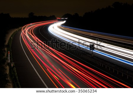 Long exposure photo of traffic on the move at night on the M40 motorway in England - stock photo