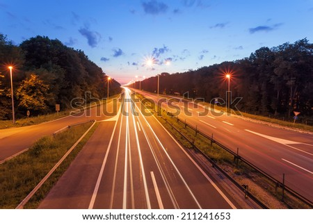Long exposure photo on a highway with light trails at dusk - stock photo