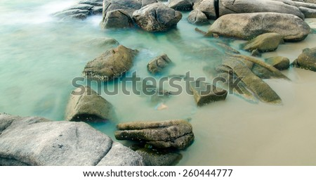 Long Exposure Seascape with running waves on the rocks at the beach trip at rayong : soft focus - stock photo