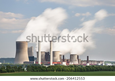 Long exposure shot of a coal-fired power station in the distance in agricultural landscape. The power station Niederaussem has the second highest cooling tower in the world with a height of 200m. - stock photo