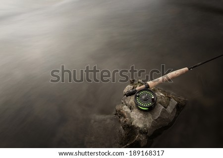 Long exposure shot of a fly rod in a fast moving trout stream. - stock photo