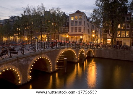 Long exposure shot of Amsterdam at night showing bicycles on a bridge over a canal - stock photo