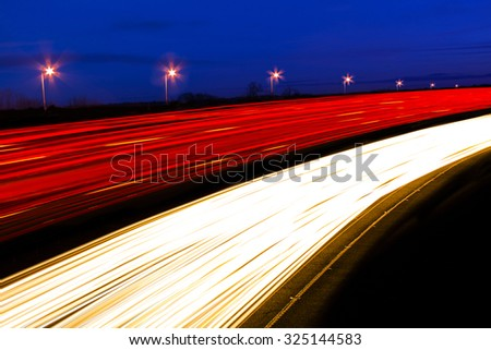 Long exposure shot of cars and lorries leaving light trails as they pass by quickly  - stock photo
