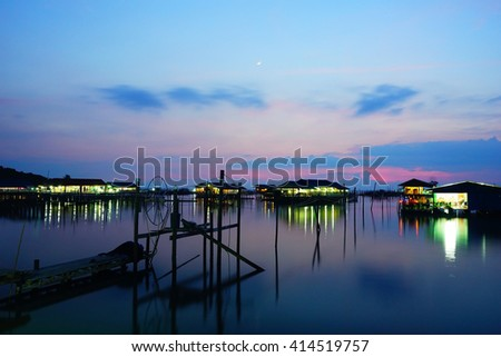 Long exposure shot over houses on night view in Lake at Songkhla Thailand during sunset.Motion blur,soft focus due to slow shutter speed. - stock photo
