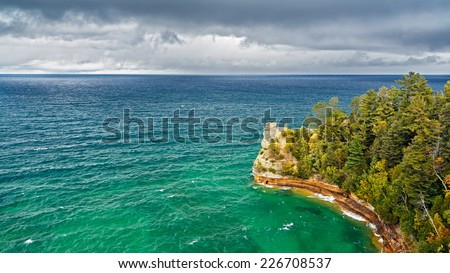 Long exposure shows the whitewater of the Hurricane River flowing across a beach and into Lake Superior surf on a cloudy day at Pictured Rocks National Lakeshore in Michigan's Upper Peninsula. - stock photo