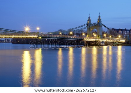 Long exposure side shot of Hammersmith Bridge, in West London, over the river Thames at dusk. - stock photo