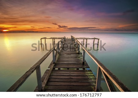 Long Exposure Sunrise Seascape with Abandon Jetty, Teluk Tempoyak, Pulau Pinang, Malaysia - stock photo