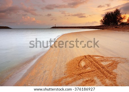 Long Exposure Sunrise Seascape with Money Symbols written on the Sand and Lighthouse as a middleground. Soft Focus, Motion Blur due to Long Exposure Shot. Copy Space Area - stock photo