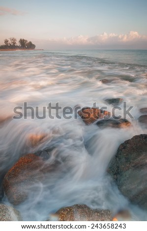 Long Exposure Sunrise Seascape with running waves on the rocks at the beach (soft focus, shallow DOF, slight motion blur)  - stock photo
