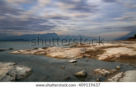 long exposure sunset landscape on Garda lake. Italy. Rocks and clouds - stock photo