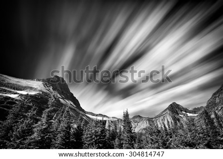 Long exposure view of the Rocky Mountains in Glacier National Park featuring dramatic streaking clouds - stock photo