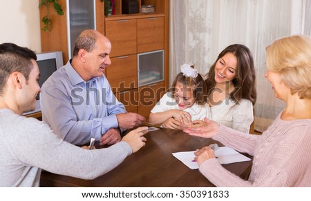 Long family with grand children sitting at table with cards - stock photo