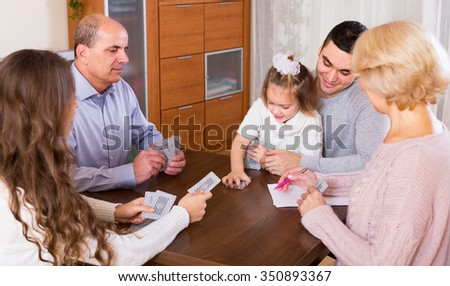 Long family with grand children sitting at table with cards indoor - stock photo