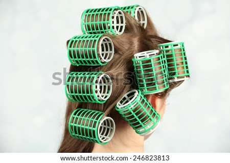Long female hair during hair dressing with curler, close-up, on light background - stock photo