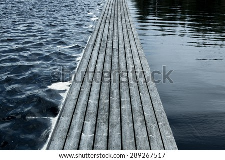 Long floating wooden bridge on water surface. - stock photo