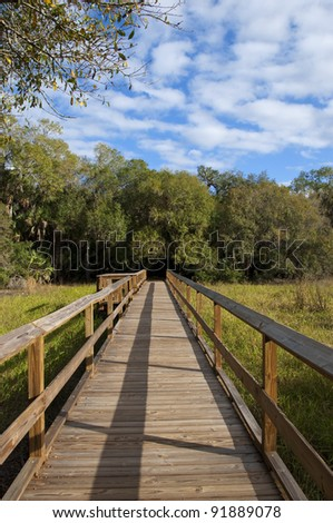 Long footbridge with interesting shadows on a nature walk trail in Myakka River State Park in Florida, with viewing alcove midway down. - stock photo