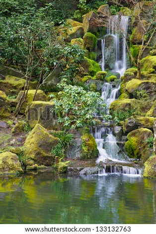 Long Garden Waterfall over moss covered boulders and green vegetation - stock photo