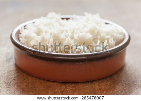 Long grain rice in a terracotta bowl on a wooden surface - stock photo