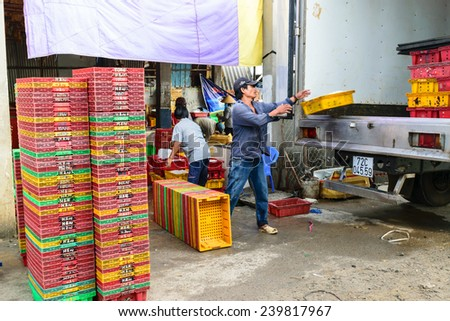 LONG HAI, VIETNAM, DECEMBER 21 2014: Fishers's Daily life, fishing village with a lot of fishes in fishing basket at traditional fish market on the Long Hai harbour. - stock photo