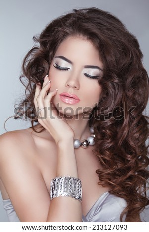 Long hair. Beauty fashion brunette woman model with wavy hairstyle and professional makeup. Jewelery.  - stock photo