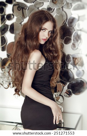 Long hair. Fashion attractive girl model in short black dress posing against mirrors wall at interior - stock photo