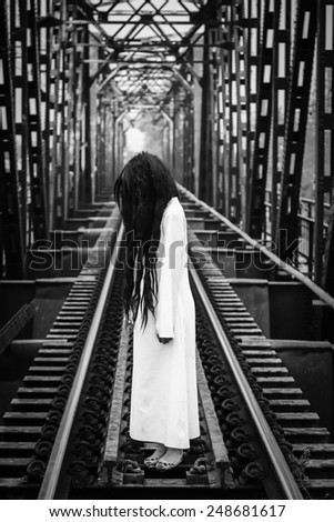 Long hair girl ghost standing on railroad - stock photo