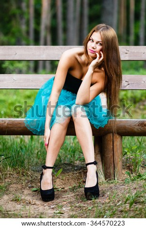 Long-hair girl sitting on  bench. - stock photo