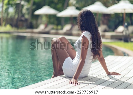 Long Hair Slim Asian Indian Woman Unwinding at Poolside on One Sunny Day. - stock photo