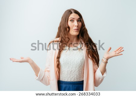 long-haired beautiful brunette girl does not know what to do and spread her arms to the sides - stock photo