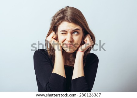 long-haired beautiful young brunette woman covering her ears with her hands, isolated on a white background - stock photo