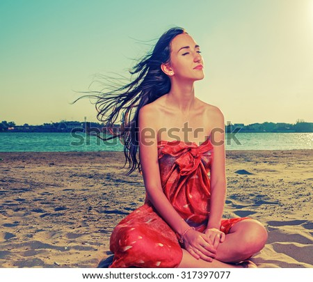 Long haired brunette meditate on sandy beach with flattering hair fly with the wind - stock photo