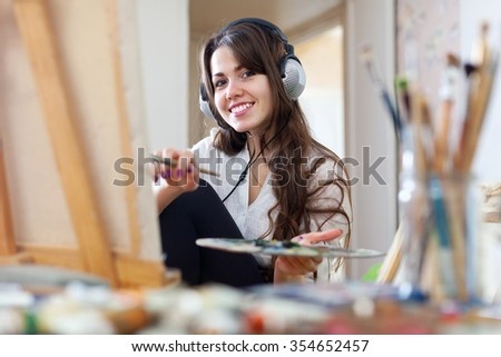Long-haired female artist  in headphones paints picture on canvas with oil paints in   - stock photo