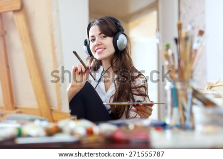 Long-haired girl in headphones  paints with oil colors and brushes on canvas  - stock photo