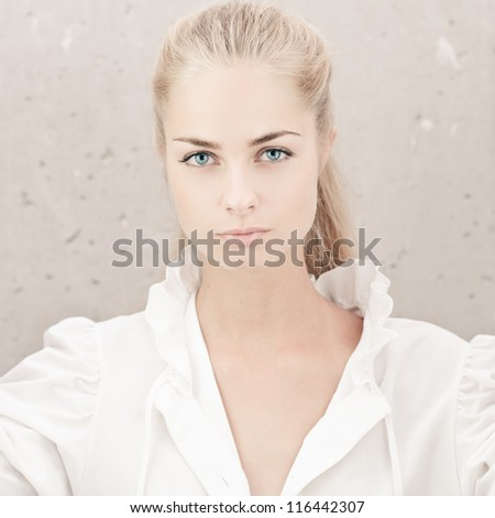 Long haired girl over grunge wall - stock photo