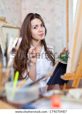 Long-haired girl paints with oil colors and brushes on canvas in workshop interior - stock photo