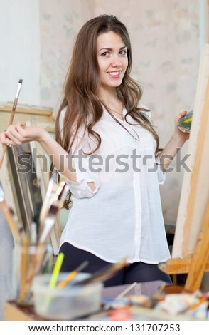 Long-haired girl paints with oil colors on easel - stock photo