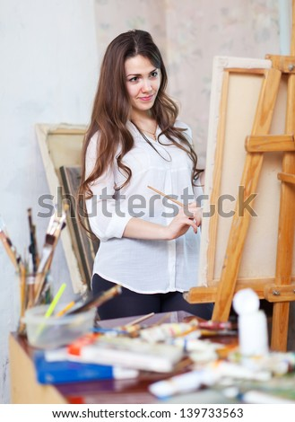 Long-haired girl paints with oil colors on easel in workshop interior - stock photo