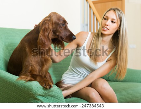 Long-haired girl sitting on sofa with red Irish setter. Focus on dog - stock photo