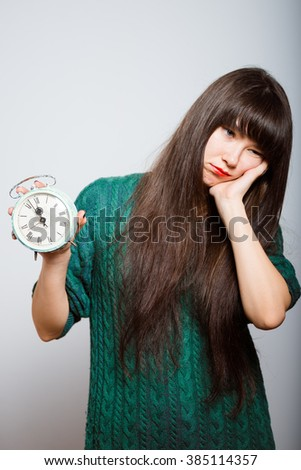long-haired girl wants to sleep with an alarm clock, a business woman isolated on a gray background - stock photo