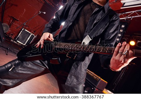 Long haired guitarist is playing and singing - stock photo