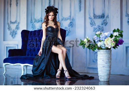 Long haired sensual brunette with a wreath of black flowers sitting on a blue sofa - stock photo