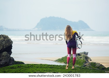 Long-haired surfer girl watching waves standing on the beach - stock photo