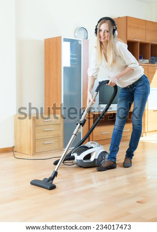 Long-haired woman with vacuum cleaner cleaning her living room - stock photo