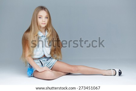 Long haired young girl posing in studio on light grey background - stock photo