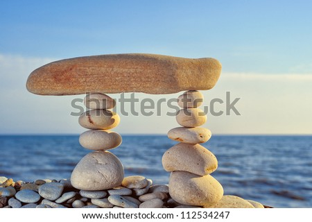 Long horizontal stone between a pebble piles - stock photo
